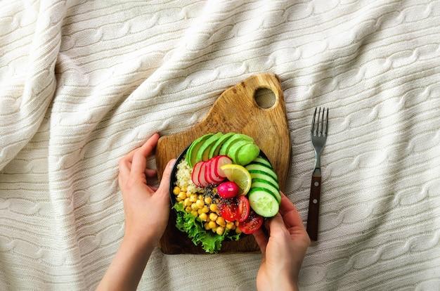 Fille en jeans tient dans la fourchette des mains, repas de petit déjeuner végétalien dans un bol avec avocat, quinoa, concombre, radis