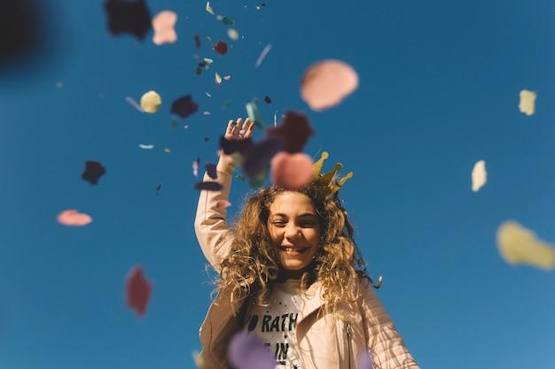 Fille jetant des confettis