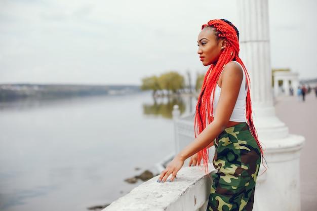 Une fille jeune et élégante à la peau foncée avec des dreads rouges marchant dans le parc de l'été près de la rivière