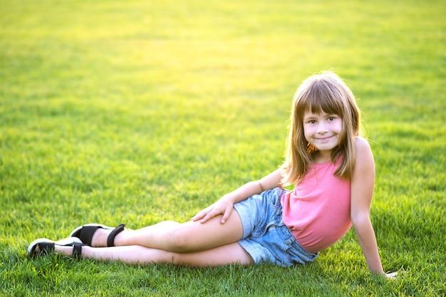 Fille jeune enfant heureux au repos assis sur la pelouse d'herbe verte sur une chaude journée d'été.