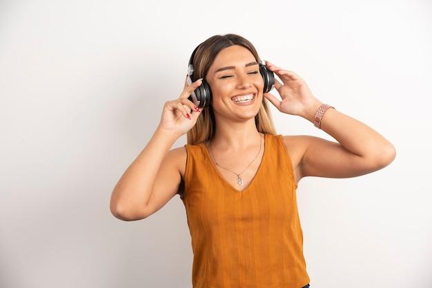 Fille de jeune femme dans des vêtements décontractés posant avec des écouteurs.