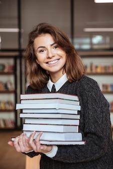 Fille ou jeune femme avec une pile de livres dans la bibliothèque