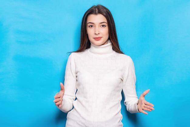 Fille de jeune femme surprise en posant blanc décontracté isolé sur fond bleu turquoise. concept de mode de vie des gens. maquette de l'espace de copie. gestes démontrant la taille avec un espace de travail horizontal