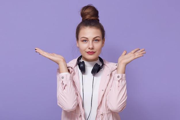 Fille jeune femme en veste rose posant isolé sur fond lilas, écouter de la musique, posant avec un casque autour du cou, écartant les mains, regarde la caméra.