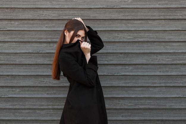 Fille jeune mannequin à la mode en manteau noir couvre son visage