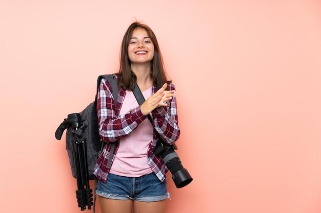 Fille jeune photographe sur mur rose isolé applaudissant