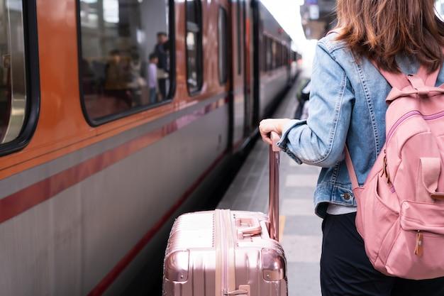Fille jeune voyageur en veste jeans avec sac rose et bagages en attente pour le train sur la plate-forme, copie espace, concept de voyage ou de transport