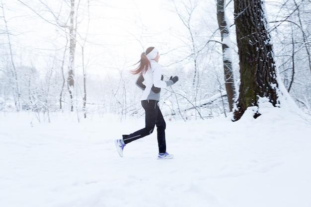 Fille jogging dans les bois d'hiver