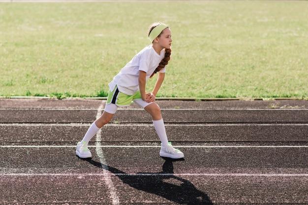 Fille de jogging sur une soirée d'été ensoleillée, allongée sur tapis roulant, stade, entraînement physique, retour à l'école, fatiguée.