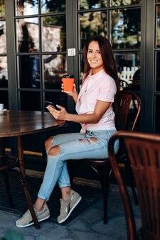 Fille joliment habillée, assis dans le café, boire du café.