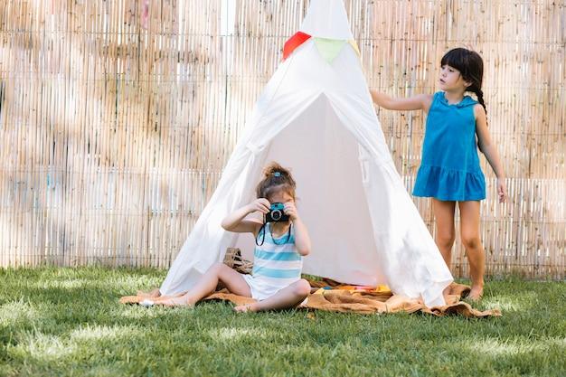 Fille jouant au photographe dans la tente
