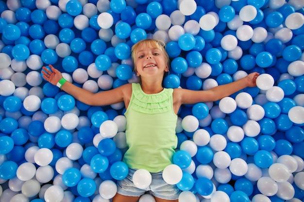 Fille jouant avec le ballon dans la salle de jeux.