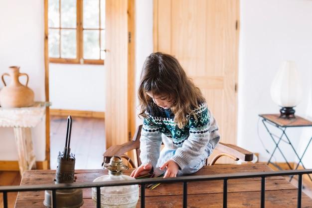 Fille jouant avec des bâtons en plastique sur un bureau en bois