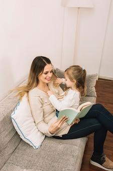 Fille jouant avec les cheveux et accessoires de lecture maman