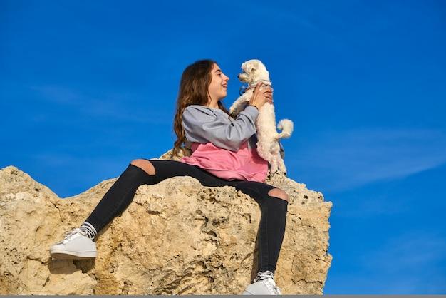 Fille jouant avec un chien chiot maltichon sur un rocher