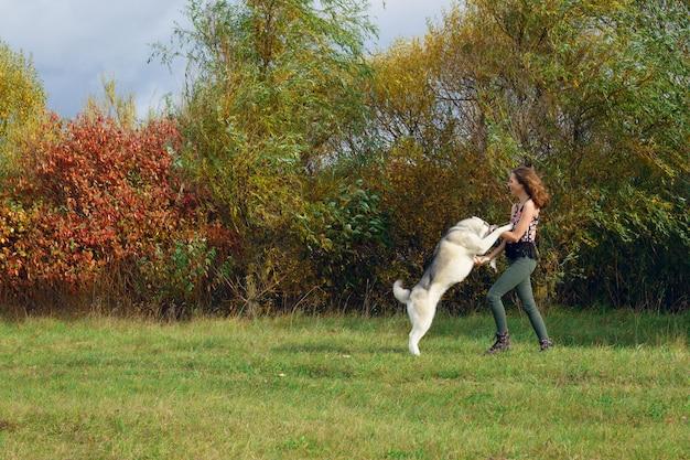 Fille jouant avec un chien husky dans le parc de la ville. jogging avec chien.