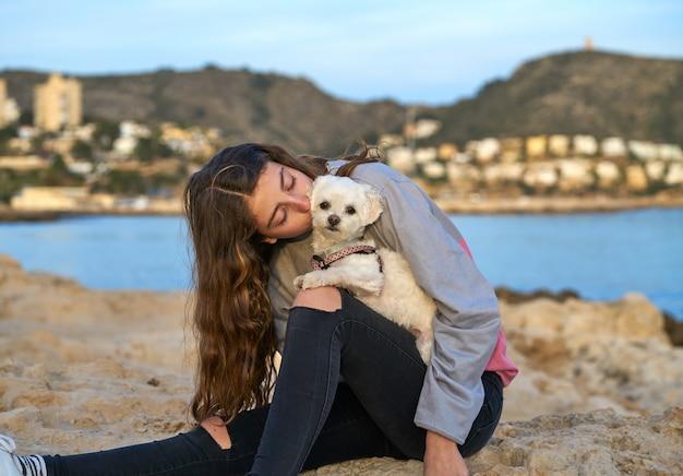 Fille jouant avec un chien maltichon à la plage