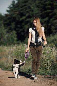 Fille jouant avec chiot border collie noir et blanc sur le chemin de la forêt