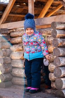 Fille jouant dans une maison en bois