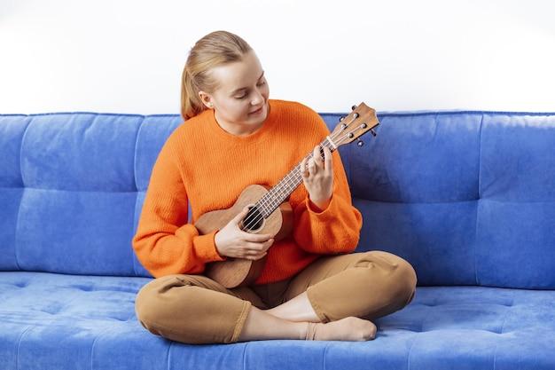 Fille jouant du ukulélé à la maison sur le canapé
