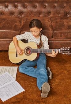 Fille jouant de la guitare à la maison