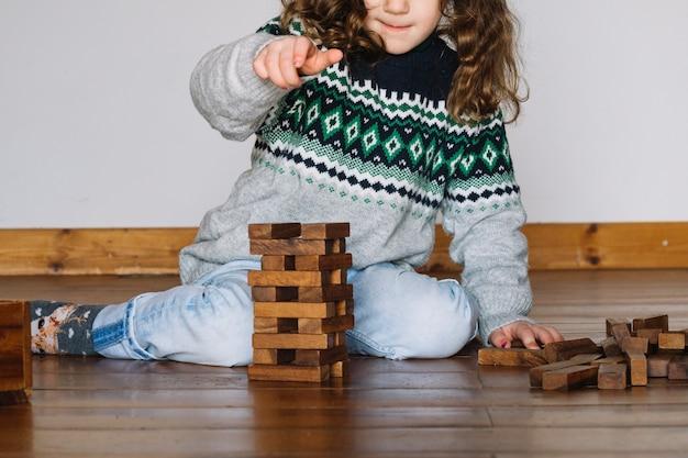 Fille jouant jenga à la maison