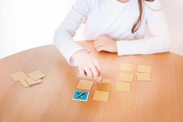 Fille jouant à un jeu, aptitude mentale, mémorisation, jeu de société, jouer pendant les vacances, loisirs, isolement, temps avec avantages, développer l'esprit
