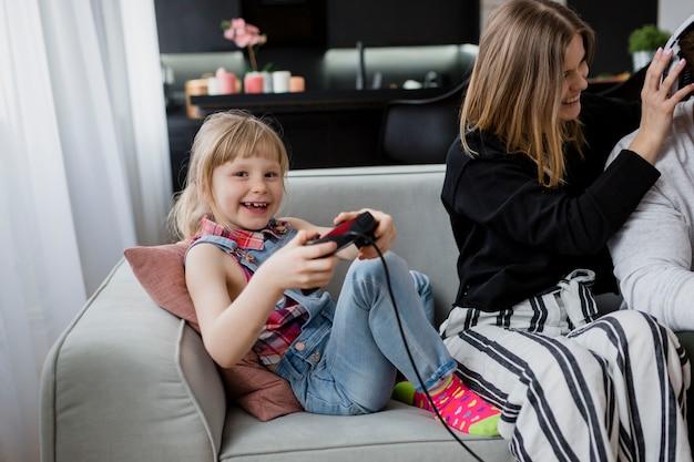 Fille jouant à un jeu vidéo près des parents