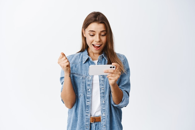 Fille jouant à des jeux vidéo sur smartphone et gagnant, célébrant, debout contre un mur blanc