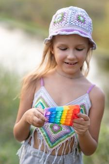 Fille jouant avec un jouet pop-it, dans la nature