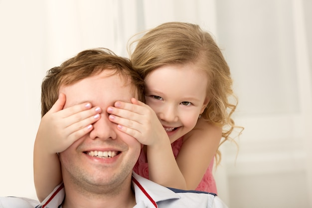 Fille jouant avec le père en fermant les yeux