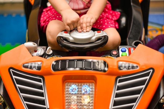 Fille jouant sur une voiture de jouet