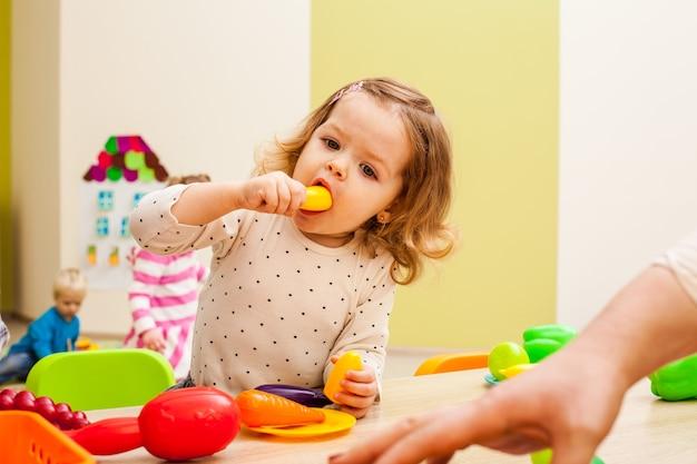 Une fille joue avec des articles ménagers pour enfants et des fruits artificiels à table. équipement de cuisine