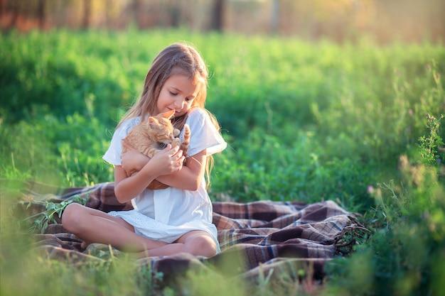 La fille joue avec un chaton roux dans la rue. pays fille jouant avec un chat. enfant au repos à la ferme.