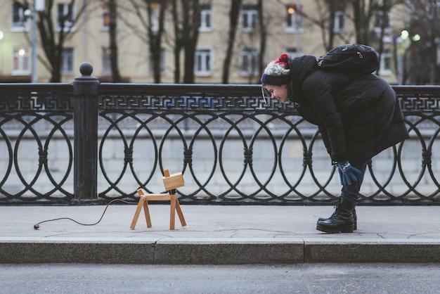La fille joue dans la rue avec un chien imaginaire, qui est en fait une lampe