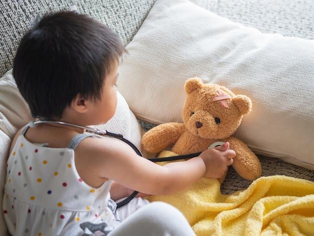 Fille joue docteur avec stéthoscope et poupée d'ours