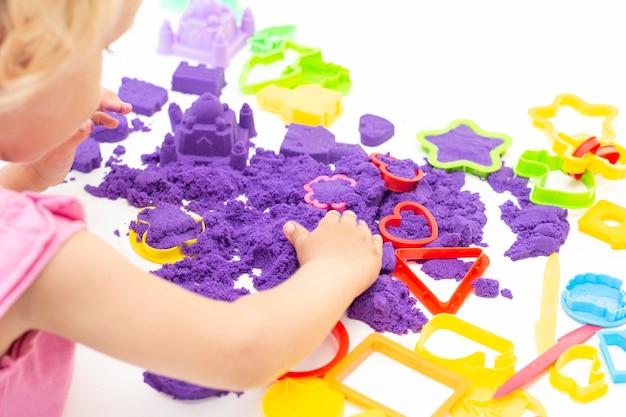 Fille joue du sable cinétique en quarantaine. blonde belle fille sourit et joue avec du sable violet sur un tableau blanc.