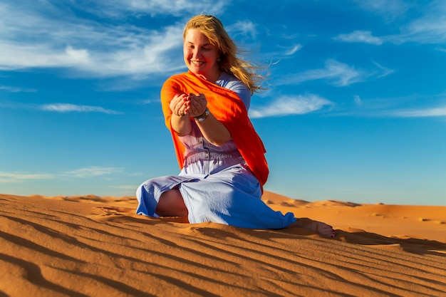Fille joue avec du sable dans le désert du sahara. erg chebbi, merzouga, maroc.