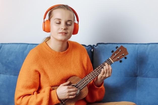 La fille joue du ukulélé avec des écouteurs dessus