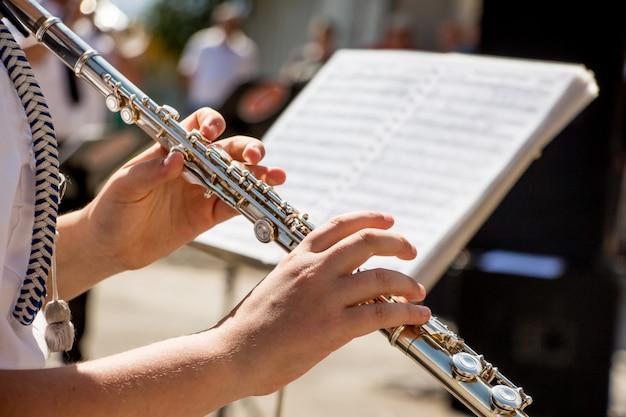 Fille joue de la flûte. flûte dans les mains de la jeune fille pendant le concert. musicien professionnel jouant de la flûte lors d'un concert de musique classique
