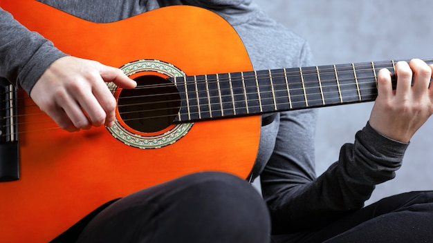 Fille joue une guitare acoustique couleur orange sur fond gris