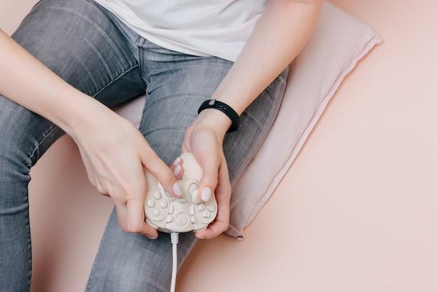Fille joue à des jeux assis sur l'oreiller. joystick rose