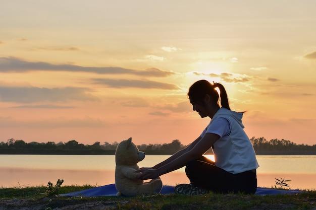 La fille joue avec un ours en peluche.