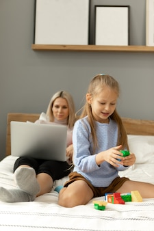 La fille joue pendant que maman regarde l'écran du portable. fonctionne ou effectue des achats en ligne.