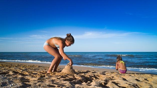 Fille jouer au bord de la mer, faire des pyramides de sable