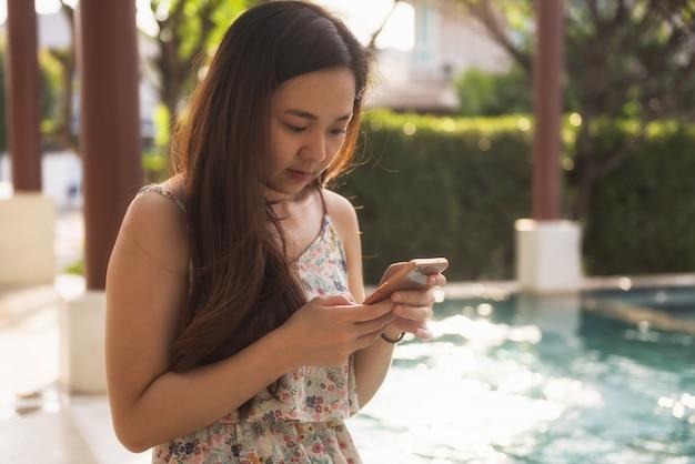 Fille jouer aux médias sociaux et faire du shopping à la piscine