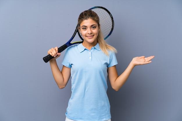 Fille de joueur de tennis adolescent sur un mur gris avec une expression faciale choquée