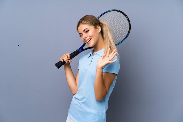 Fille de joueur de tennis adolescent sur mur gris saluant avec main avec une expression heureuse