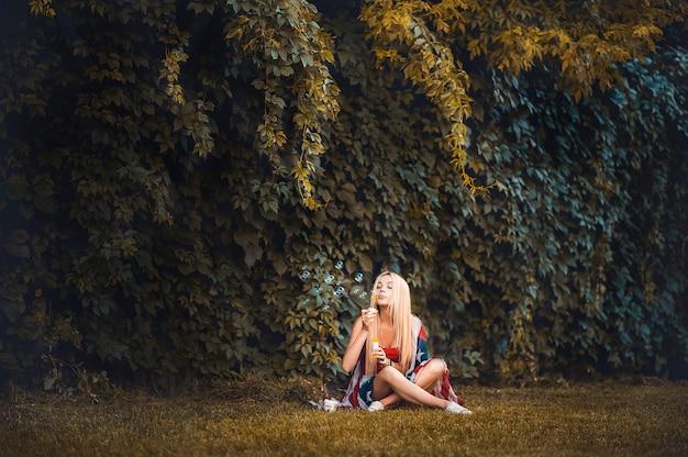 Fille le jour de l'indépendance des états-unis. la blonde est assise sur la pelouse après les vacances. jour de l'indépendance des états-unis, foulard drapeau américain, bulles de savon