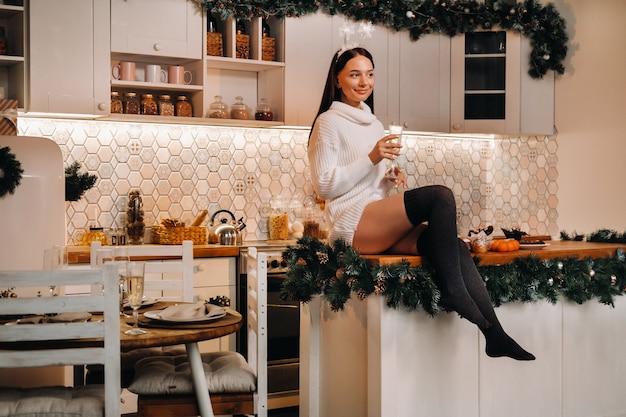 Une fille le jour de noël est assise sur la table de la cuisine et tient une coupe de champagne. femme le soir du nouvel an avec du champagne